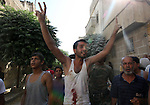 A Syrian man shots slogans after removing a body from under the rubble following a reported barrel-bomb attack by Syrian government forces, in the Tariq al-Bab neighbourhood in the northern city of Aleppo, on August 21, 2015. Photo by Ameer al-Halbi