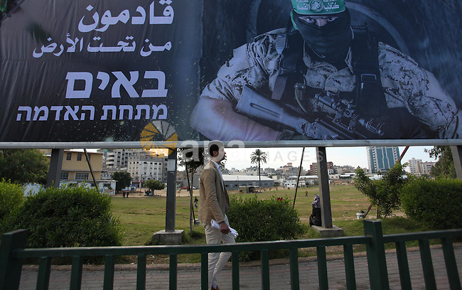 A Palestinian man walks past a mural depicting a Member of the Ezzedine al-Qassam Brigades, the military wing of the Palestinian Islamist movement Hamas, in Gaza city, on December 18, 2016. The Palestinian Hamas movement in Gaza blamed Israel on Saturday for the killing in Tunisia this week of a Tunisian Mohammed Zawari, who was gunned down near the city of Sfax on Thursday, had been a member of the group for 10 years and had been supervising its drone programme. Photo by Ashraf Amra