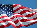 Waving American flag against a blue sky background.