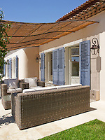 On the rear terrace a cane awning shades a comfortable rattan sofa and matching armchairs