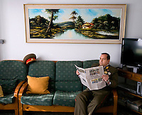 A portrait of Alejandro Cao de Benos, photographed in the village of Salomo in northeast Spain reading a newspaper in his uniform. As a Korean-Spanish communist, Alejandro is the president of the Korean Friendship Association (KFA) and has been an advocate of the Democratic People's Republic of Korea (North Korea) since 1990. His Korean name is Zo Sun-il (Korea is One) and he works as an honorary Special Delegate of the DPRK's Committee for Cultural Relations with Foreign Countries - a North Korean government spokesman in Europe.
