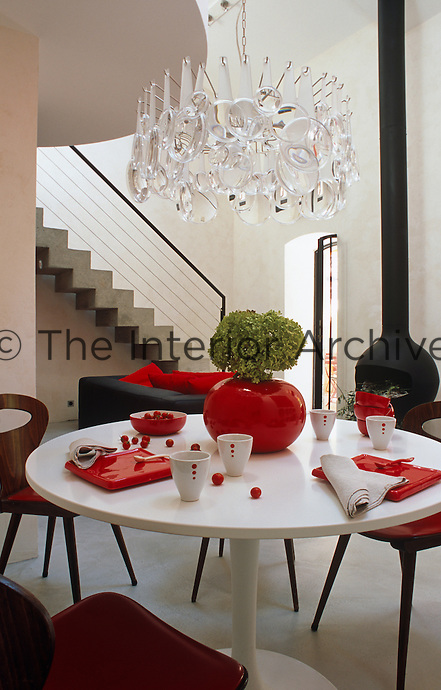 A contemporary chandelier made of magnifying glasses is supended over a casually laid Saarinen tulip table
