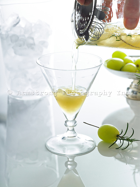 Grape juice and rosemary cocktail being poured from a strainer into a cocktail glass