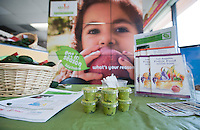 Table for the Occidental College UEPI CA Farm to School program, in which staff talks to local residents and hands out bags of avocados and taste samples in Mother's Nutritional Center in the Highland Park neighborhood of Los Angeles. The program is intended to promote locally grown fruits and vegetables. (Photo by Marc Campos, Occidental College Photographer)