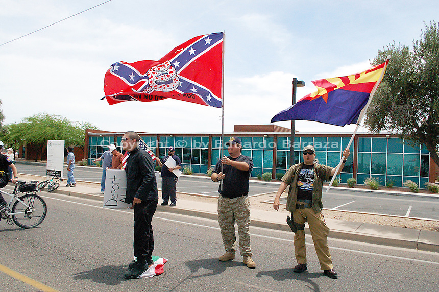 """Phoenix, Arizona – Neo-Nazi and border vigilante Jason """"J.T."""" Ready (center) waves a Gadsden Flag during an immigrant protest in Phoenix, Arizona on May 2, 2009. To his right is Thomas Colletto (AKA Vito Lombardi) stepping on a Mexican flag. Coletto would later leave Ready's vigilante group. The man to his left is unidentified. Ready would kill four members of a family three years later on the very same date –May 2, 2012– before taking his own life. The victims were Lisa Mederos, Amber Mederos, baby Lilly Mederos, and Amber's fiancé Jim Hiott. The massacre occurred in the town of Gilbert, Arizona, about 25 miles southeast of Phoenix. Ready was Lisa's boyfriend and according to police, a domestic violence incident may have caused the killings. Photo by Eduardo Barraza © 2009"""