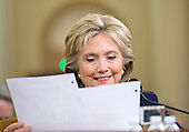Former United States Secretary of State Hillary Rodham Clinton, a candidate for the 2016 Democratic Party nomination for President of the United States, smiles as she reads a memo from Ambassador J. Christopher Stevens, the US envoy to Libya who was killed in the terror attack in Bengazi on September 11, 2012 as she testfies before the US House Select Committee on Benghazi on Capitol Hill in Washington, DC on Thursday, October 22, 2015.<br /> Credit: Ron Sachs / CNP<br /> (RESTRICTION: NO New York or New Jersey Newspapers or newspapers within a 75 mile radius of New York City)