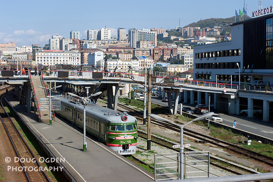 The train terminal with the marine terminal on the right and buildings of Vladivostok in the background, Russia