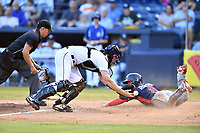 Asheville Tourists catcher Willie MacIver (23) attempts to catch the ball as Ricardo Rodriguez (8) slides across home plate in front of umpire Rene Gallegos during a game against the Rome Braves at McCormick Field on July 19, 2019 in Asheville, North Carolina. The Braves defeated the Tourists 4-1. (Tony Farlow/Four Seam Images)