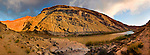 A panoramic photo of sunset on the San Juan River, Utah. Raplee Anticline rises to West.
