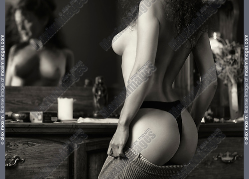 Sensual erotic black and white portrait of a sexy beautiful topless half naked woman dressing up in front of a mirror