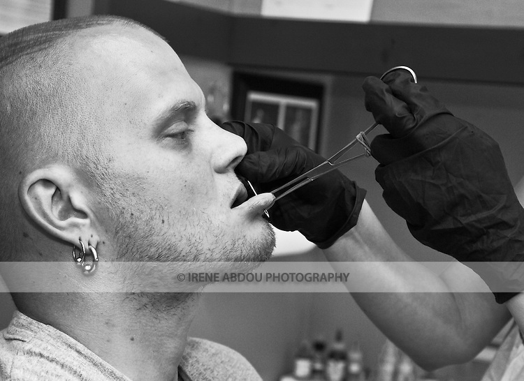 Sean Jeweii, a body piercer in Rockland Maine, gives his apprentice some practice by allowing her to pierce his chin.