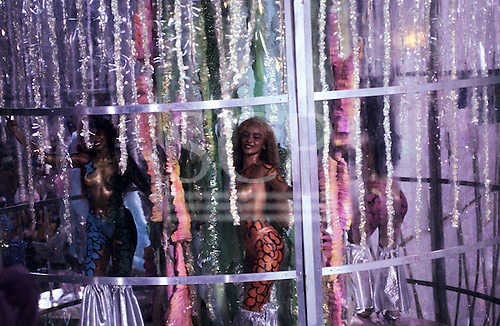 Rio de Janeiro, Brazil. Carnival; samba dancers with body paint in a cage of dangling tinsel.