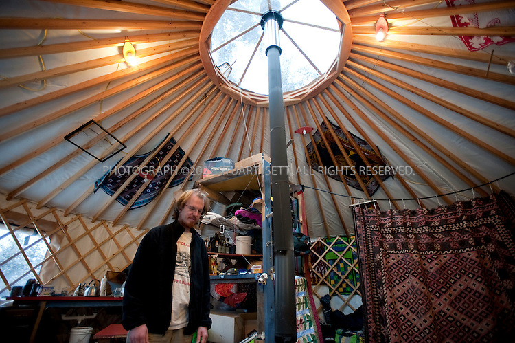 12/11/2009--Seldovia, Alaska, USA..Bretwood Higman ('Hig') stays warm in his family's yurt in Seldovia, Alaska...The yurt is made by Nomad Shelter in Homer, Alaska, and cost about $14,000.  Bretwood Higman ('Hig'), 33 and Erin McKittrick, 30, built it in November, 2008 on land owned by Hig's mother in Seldovia. The yurt is 24' in diameter, the ceiling is over 12' in the middle, 7' around the edge. It has no running water but does have electricity and internet access...McKittrick grew up in Seattle and met Higman, from Seldovia, at Carleton College in 2001.  In June 2007, the couple left Seattle for the Aleutian Islands, traveling 4000 miles solely by human power through some of the most rugged terrain in the world; their adventure has recently been published in a book written by McKittrick with Hig's photographs titled, 'A Long Trek Home: 4,000 Miles by Boot, Raft, and Ski'...Together, the couple also run a small environmental non-profit, Ground Truth Trekking, which uses trekking to explore the complexities of natural resource issues.  The couple lives with their 10 month old son son, Katmai, in Seldovia, Alaska, a 300 person village just off the end of the road system...©2009 Stuart Isett. All rights reserved.