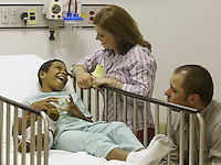 Derick Byrd, left, with his mother Terra and father Matt, discuss what will happen to Derick during his surgery at Children's Hospital, Friday June 17, 2005, in Columbus, Ohio. Derick's surgery was a non-invasive procedure using an electromagnetic field to create heat that softens a polymer, allowing Derick's plastic and titanium prosthesis to expand.<br />