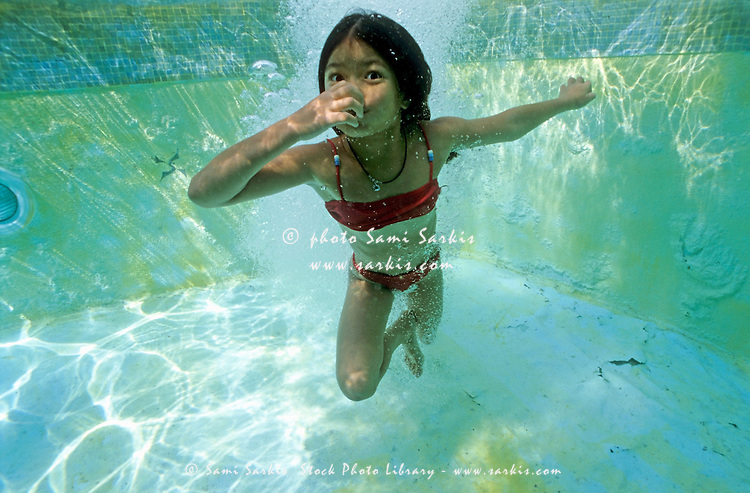 Young girl holding her breath underwater in a swimming pool, Provence, France.