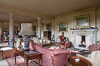 The long reception room is furnished with sofas and armchairs upholstered in a pink damask fabric