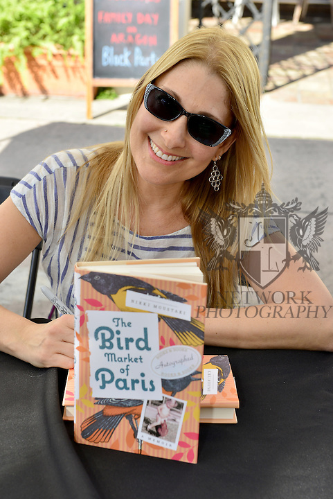 "CORAL GABLES, FL - JANUARY 09: Author Nikki Moustaki ""The Bird Market of Paris: A Memoir"" sign copies of her books at The Family Day Block Party first annual block party with activity in Coral Gables art Cinema and Coral Gables Museum presented by Books and Books at Aragon Avenue in Coral Gables on Saturday January 9, 2016 in Coral Gables, Florida.  ( Photo by Johnny Louis / jlnphotography.com )"