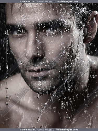Dramatic closeup portrait of a man face wet from water pouring on it