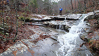 NWA Democrat-Gazette file/FLIP PUTTHOFF<br /> Water cascades over rock after sufficient rainfall soaks the region. Tom Mowry admires a small cascade in Dismal Hollow on the hike Nov. 30, 2015 to the Glory Hole waterfall.