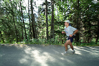 A runner participating in the 2004 Resurrection Pass Trail 100-Miler and 50-Miler ultramarathons makes his way up Palmer Creek Road in the Chugach National Forest near Hope, Alaska.
