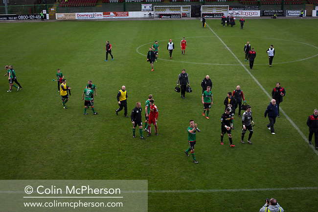 Players and officials leaving the pitch at The Oval, Belfast after Glentoran (in green) hosted city-rivals Cliftonville in an NIFL Premiership match. Glentoran, formed in 1892, have been based at The Oval since their formation and are historically one of Northern Ireland's 'big two' football clubs. They had an unprecendentally bad start to the 2016-17 league campaign, but came from behind to win this fixture 2-1, watched by a crowd of 1872.