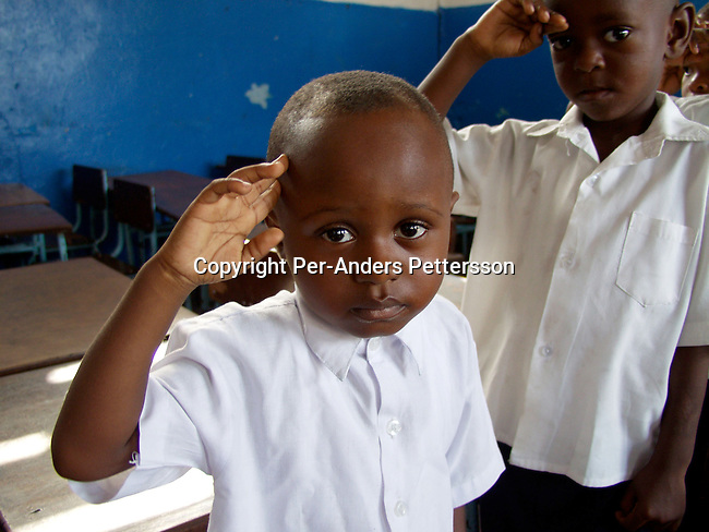 dicocon00118 .Country  Congo.  Education. Mpoyo Dan, age 4, (left) during the singing of patriotic military song in his class on February 28, 2002 at ÒBambiniereÓ a school in Lingwala district, in Kinshasa, Congo. The teacher tells them about the occupation of Rwandan and Ugandan troops in the country..©Per-Anders Pettersson/iAfrika Photos