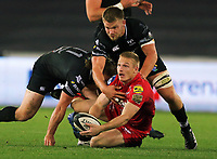 Johnny McNicholl of the Scarlets (with ball)makes a pass while held down by Dan Biggar of the Ospreys during the Guinness PRO14 Round 6 match between Ospreys and Scarlets at The Liberty Stadium , Swansea, Wales, UK. Saturday 07 October 2017