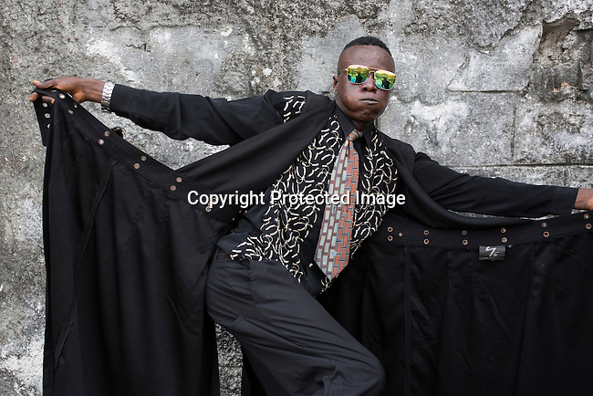 """KINSHASA, DEMOCRATIC REPUBLIC OF CONGO - FEBRUARY 10: A Sapeur poses for a portrait with his designer label clothes while paying his respects to Stervos Nyarcos, the founder of the kitendi religion, which means clothing in local language Lingala. Nyarcos was known as the leader of the Sape movement, at Gombe cemetery on February 10, 2017 in Kinshasa, DRC. The word Sapeur comes from SAPE, a French acronym for Société des Ambianceurs et Persons Élégants. or Society of Revellers and Elegant People. and it also means, .to dress with elegance and style"""". Most of the young Sapeurs are unemployed, poor and live in harsh conditions in Kinshasa, a city of about 10 million people. For many of them being a Sapeur means they can escape their daily struggles and dress like fashionable Europeans. Many hustle to build up their expensive collections. Most Sapeurs could never afford to visit Paris, and usually relatives send or bring clothes back to Kinshasa. (Photo by Per-Anders Pettersson)"""