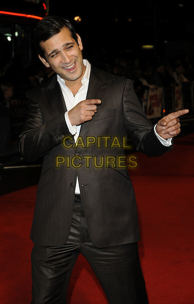 JIMI MISTRY.The 'West Is West' premiere, Day 7 of the London Film Festival, Leicester Square, London, England..October 19th, 2010.half length black suit white shirt brown mouth open hands finger pointing double gun funny.CAP/CAN.©Can Nguyen/Capital Pictures.