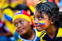 A Colombian girl, with the national flag painted on her face, watches the football match between Colombia and Uruguay at the FIFA World Cup 2014, in a park in Cali, Colombia, 28 June 2014.