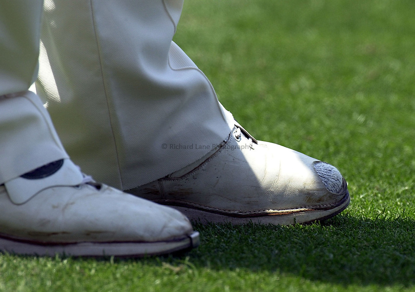 England's bowler Andy Caddick has the toe cut out of his shoe on the second day of the Ashes Cricket Test Match against Australia at the Gabba Cricket Ground, Friday November 8th, 2002.