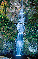738600001 partially frozen multnomah falls cascades down a cliff face in fronto of a trail brigde in columbia river gorge national recreation area oregon