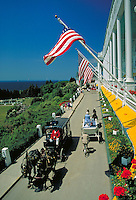 Hotels enclosed carriages and carriage with newlyweds on drive in front of hotel's flag draped porch, longest in the world. Mackinac Island Michigan USA.