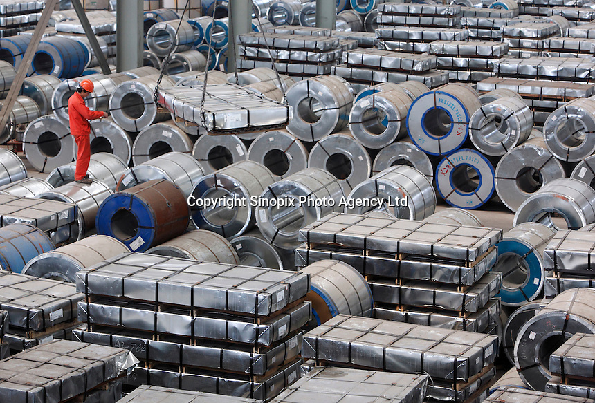 A worker stands on top of stacks of steel products at a warehouse run by the Shanghai Yirong Trading Company Ltd in Shanghai, China..10 Apr 2009
