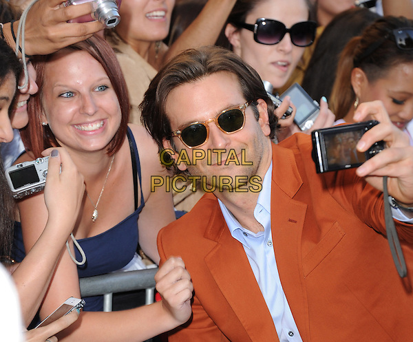 "Bradley Cooper.""The Hangover Part III"" Los Angeles Premiere held at the Westwood Village Theater, Los Angeles, California, USA..May 20th, 2013.half length sunglasses shades mobile camera fans crowd posing orange suit blue shirt taking picture photographs                                                 .CAP/DVS.©DVS/Capital Pictures"