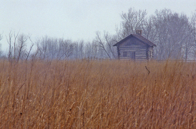 A re-created prairie settler's log cabin sits in the autumn fog, Goose Lake Prairie State Park, LaSalle County, Illinois