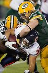 Green Bay Packers linebacker A.J. Hawk (50) and defensive back Charlie Peprah (26) tackle Chicago Bears running back Kahlil Bell (32) during a week 16 NFL football game on December 25, 2011 in Green Bay, Wisconsin. The Packers won 35-21. (AP Photo/David Stluka)