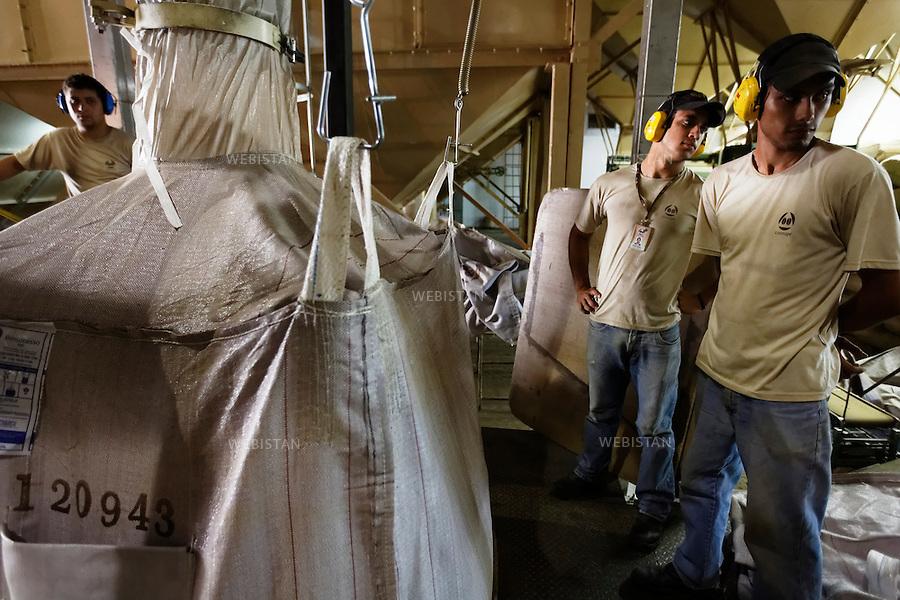 Bresil, etat Minas Gerais, Guaxupe, entrepot Cooxupe, 31 octobre 2012.<br /> <br /> Cooxupe est l&rsquo;une des plus grosses cooperatives bresiliennes de cafe. Elle a signe un partenariat avec Nespresso dans le cadre du Programme AAA. Elle dispose de plusieurs sites dont celui de Guaxupe qui s'est dote, en 2008, d'un laboratoire ultra-moderne d'analyse du cafe.<br /> Etape de la mise en liner, supervisee par plusieurs ouvriers agricoles.<br /> Un liner est  un sac dont la taille est celle de l'espace interieur d'un conteneur de 20 pieds (TEU, Twenty-foot Equivalent Unit). Il se fixe a l'aide de crochets dans les coins superieurs, les grains de cafe sont souffles a l'interieur, ce qui remplit graduellement le conteneur. <br /> Reportage les Chants de cafe_soul of coffee, realise sur les acteurs terrain du programme de developpement durable Triple AAA de Nespresso.<br /> <br /> Brazil, Minas Gerais, Guaxupe, Cooxupe Warehouse, October 31, 2012 <br /> <br /> Cooxupe, one of the largest coffee cooperatives in Brazil, signed a partnership with Nespresso AAA Program. Cooxupe has several sites, including one in Guaxupe, which in 2008 acquired a state-of-the-art laboratory to analyze coffee. <br /> The coffee beans are put in liners, supervised by several farm laborers. A liner is a bag with an interior space the size of a 20-foot container. The liner is held in place by hooks in the upper corners that support the coffee beans as they expand inside and gradually fill the container. <br /> Assignment: les Chants de cafe_ Soul of Coffee, implemented on the fields of Nespresso&rsquo;s AAA Sustainable Quality Program.