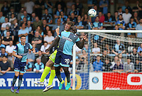 Tom Eastman of Colchester United & Adebayo Akinfenwa of Wycombe Wanderers go up for the ball during the Sky Bet League 2 match between Wycombe Wanderers and Colchester United at Adams Park, High Wycombe, England on 27 August 2016. Photo by Andy Rowland.