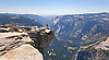 HIKER PEERS DOWNWARD 4,000 FEET FROM THE TOP OF HALF DOME TO YOSEMITE VALLEY IN YOSEMITE NATIONAL PARK, CALIFORNIA