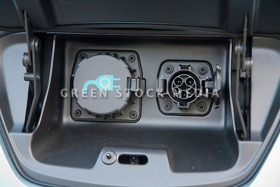Close up of the electric charging plugs compartment, in lieu of a gas tank, located on the front of the cars hood. Nissan Leaf Zero Emission Tour promotional event for the Nissan Leaf electric car that is scheduled to be released in Fall 2010. Car specs from Nissan: 5 person capacity, 90 MPH top speed, lithium-ion battery, 100 mile average range per charge. Santana Row, San Jose, California, USA, 12/5/09