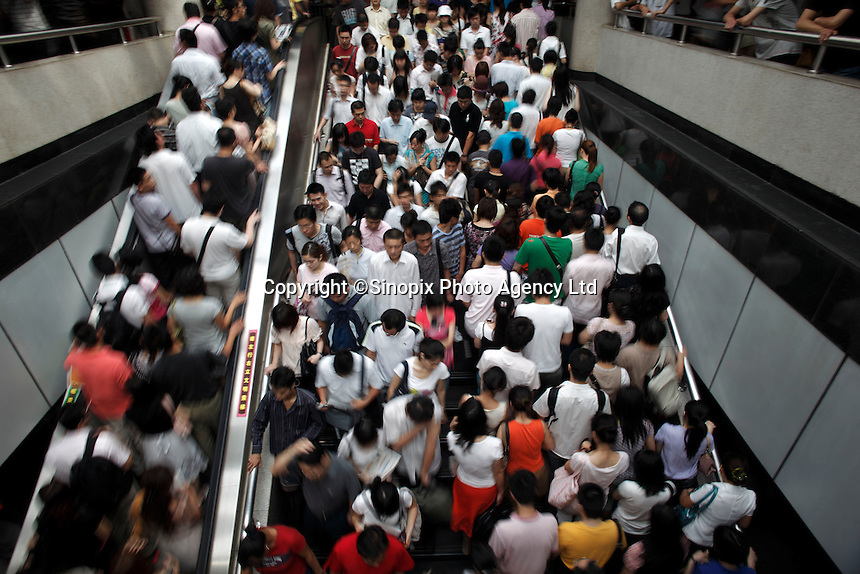 Morning commuters swarm through a major subway interchange station in downtown Shanghai, China..13 Jul 2009