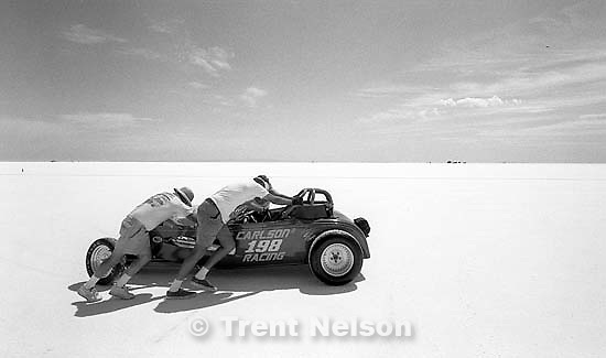 Men push a car at the Bonneville Salt Flats to watch Speed Week.<br />