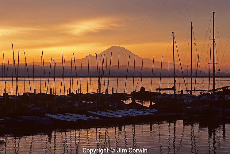 Sunrise over Lake Washington with Cascade Mountain range and marina with dramatic clouds and silhouetted masts Seattle Washington State USA