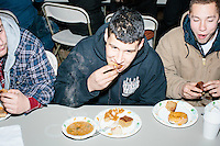 From left, Nick Belisle, Alan Clement, and Damian Thorne, all of Rochester, NH, eat before satirical presidential candidate Vermin Supreme speaks at Ten Rod Farm in Rochester, New Hampshire. The three said they are supporters of Vermin Supreme. Supreme's platform advocates a pony-based economy, using zombies to solve the energy crisis, and other outlandish ideas. Supreme has been on the New Hampshire primary ballot in 2008 and 2012, though he began running for president in 1992. Vermin Supreme will be on the Democratic party ballot in the 2016 New Hampshire primary.