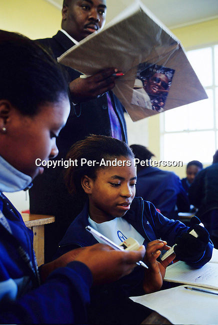 education,girl,township,classroom,.Sinelizwi Dyushu, age 12, (center) during a math class on June 17, 2004 in Yomelela primary school in Khayelitsha, the biggest black township, about 20 miles outside Cape Town, South Africa. Sinelizwe is one of about 200 children who dance in a ballet school called Dance For All, which teaches unprivileged children dance after school. Many children are talented and the discipline taught during the dance classes has helped many to improve their concentration in school. .©Per-Anders Pettersson/iAfrika Photos.......