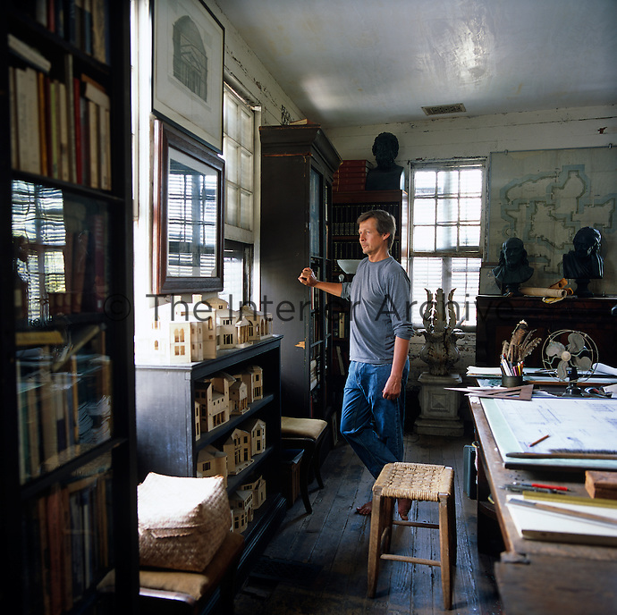 Portrait of architect Randolph Martz standing in his study