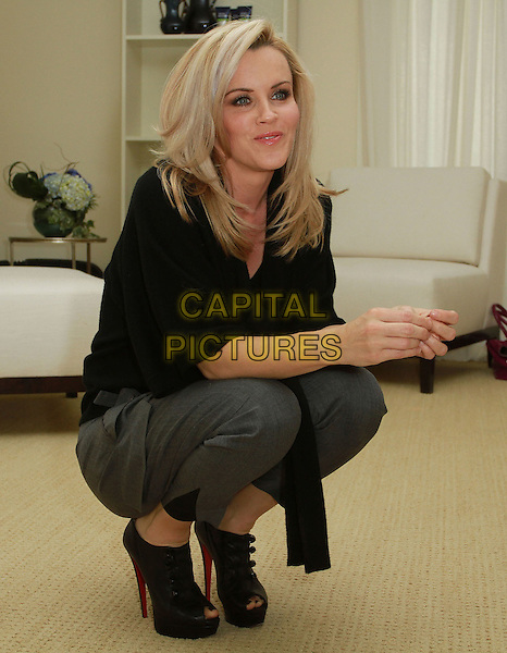 JENNY McCARTHY .At The Hospitality Suite Hosted by Pacal Mouawad held At The Nivea For Men's Mansion,  Beverly Hills, CA, USA, .14th January 2011..full length bending crouching down black  top grey gray trousers ankle boots shooboots peep toe platform shoes ankle boots christian louboutin .CAP/ADM/KB.©Kevan Brooks/AdMedia/Capital Pictures.