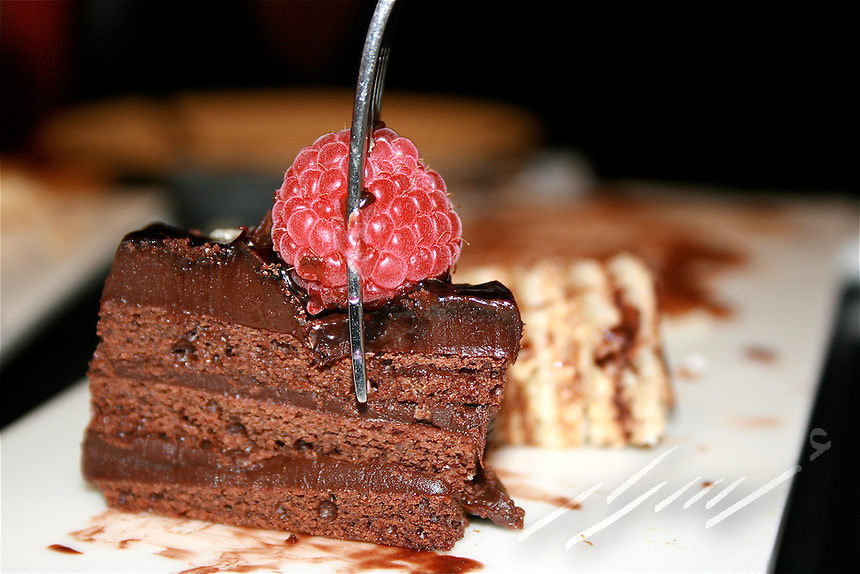 Fork running through Red Raspberry and chocolate cake.