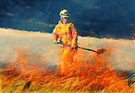 Volunteer firefighter Sue Andrews of Laramie County Fire District #8 watches a flames ignite dry grass at a fire on Happy Jack Road and County Road 110 Jan., 23, 2006 near Cheyenne.   An unattended trash fire started the blaze that burnt nearly a thousand acres west of Cheyenne.  This has been the third large grass fire in the Cheyenne area in less than a week. (AP/Michael Smith)